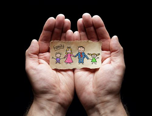 stock photo of hands open and holding a small drawing of a family