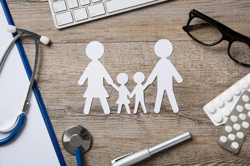 stock photo of paper cutout people on a desk with medical items