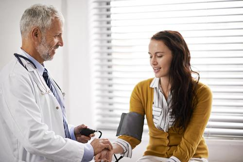 photo of a male doctor taking the blood pressure of a female patient