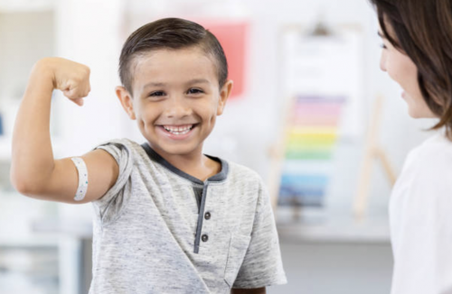 child holding up arm in flexed position with band aid on it with doctor looking on smiling